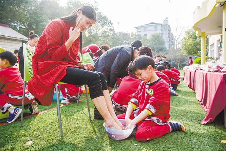 昨天,市实验幼儿园孩子们在操场上认真地给妈妈洗脚.