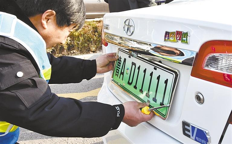 -->  12月1日,工作人员在济南市车辆管理所安装新能源汽车号牌。当日起,公安部在上海、南京、无锡、济南、深圳5个城市率先试点启用新能源汽车号牌。新能源汽车号牌号码增加一位,由5位升为6位。颜色以绿色为主色调,并增加专用标识,其中,小型新能源汽车号牌底色采用渐变绿色,大型新能源汽车号牌底色采用黄绿双拼色。   新华社发-->