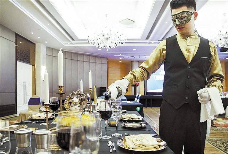 -->  西餐宴会创意摆台的要求也相当严苛,光评分细则就有几十条。选手不但要注意把握整体美感,讲究就餐礼仪,而且要注意细节准确,刀叉等餐具的摆放要精确到厘米,同时要表达参赛主题,展示选手的个性特长。   相对于中餐宴会主题摆台的大圆桌,西式宴会创意摆台用的是精致的长方形桌子。比赛现场,选手们正熟练而优雅地进行杯碟定位,餐巾折花,规范地摆放不同器皿位置,一个个让人耳目一新的西式宴会创意摆台如同一处处小风景,现代风格的,古典韵味的,高贵典雅的,充分展现出了选手们思维的开拓性与创新性。   蓝色系的流金岁月